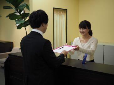 受付で記入用紙を渡される患者