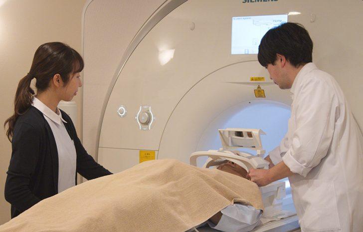 MRI検査器に患者を挿入する技師と助手